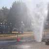A geyser of water erupts from a broken water main Friday in front of Living Word Church, 905 W. Rush, as Oklahoma Natural Gas employees wait for the City of Enid personnel to get the water shut off. The water sprayed at least 60 feet into the air. (Staff Photo by BONNIE VCULEK)