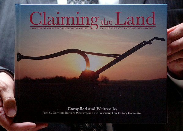"A member of the Enid United Pentecostal Church holds a copy of ""Claiming the Land,"" co-authored by Rev. Jack Garrison, Barbara Westberg and the Preserving Our History Committee for the United Pentecostal Church. Rev. Garrison, who has been the pastor at the church in Enid for 50 years, was honored by his congregation Saturday, August 02, 2014. (Staff Photo by BONNIE VCULEK)"