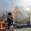 Patrick Parrish (front right) uses wet towels on Lt. Shaun Kuehn's head as the Enid Fire Department battles a barn blaze Tuesday at 4100 N. Washington. Triple-digit heat and hot, dry temperatures hindered the firefighters as engines shuttled to the scene with water. (Staff Photo by BONNIE VCULEK)