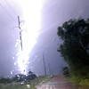 As lightning strikes, it appears like it is wrapping around a highline pole at 11:59 P.M., Sunday, July 8, 2008, on Skeleton Road, near U.S. 81. Power outages caused by lightning and heavy rains flooded city streets and rural roads throughout Garfield County when creek banks crested. (Staff Photo by BONNIE VCULEK)