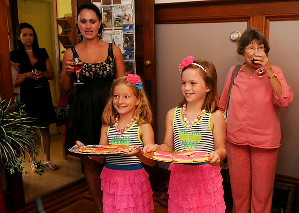 Lily Eckert and Jelani King (front, from left) offer sugar cookies to guests during the Etown Fashion Week media night at Maple Place Bed & Breakfast Monday, July 7, 2014. Proceeds from the week-long events support Loaves & Fishes, the Northwest Oklahoma Food Bank. (Staff Photo by BONNIE VCULEK)