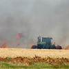 A tractor plows a fire break in a wheat field west of Waukomis Thursday afternoon. (Staff Photo by BILLY HEFTON)