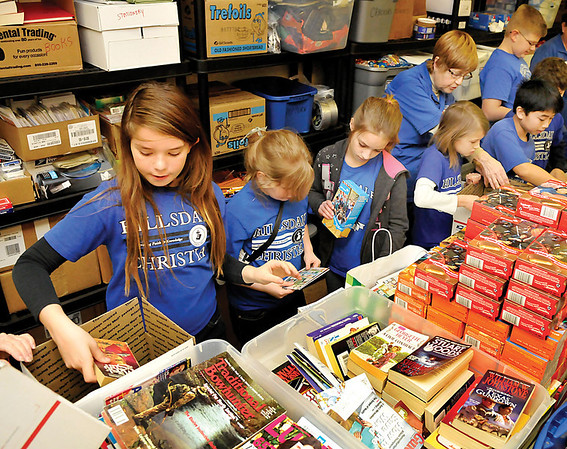 Hillsdale Christian School students pack boxes at the Blue Star Mothers shop in Oakwood Mall Thursday, Jan. 24, 2013, that will be shipped to troops serving overseas. (Staff Photo by BILLY HEFTON)