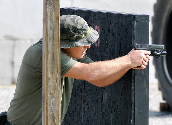 A member of the Tulsa police department SWAT team fires from cover on the pistol course Wednesday during the state SWAT competition at the Enid police department firing range. (Staff Photo by BILLY HEFTON)