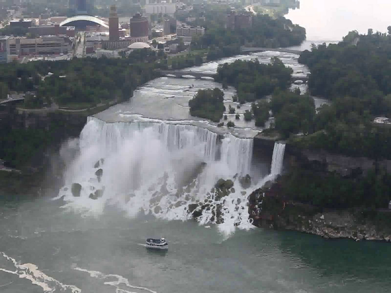 """This is American Falls from the Canadian side - viewed from the observation deck of the Skylon Tower. The """"Bridal Veil Falls""""  is on the right - with the red deck/stairs. This is the one you see on the """"Cave of the winds"""" tour and Thompson Water Seal commercial. The """"Maid of the Mist"""" is making her way with a boatload of passengers to a close encounter of the Horseshoe Falls, further upstream."""