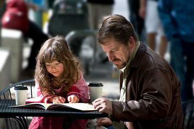 Seattle Moment This was taken on the street in Seattle near the Westlake Center on a cool fall day in 2008. This father and daughter had stopped at a Starbucks, gotten their Latte (and presumably Latte Bianco for her) and were reading in the warm sun. I love the intimacy of this moment.