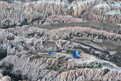 Ballooning on the Edge This photo was taken in Cappadocia (central Turkey) in April 2008. We were riding in a hot air balloon at about 1,000 feet looking down on this stark, craggy landscape and spotted these two other balloons getting ready to lift off.