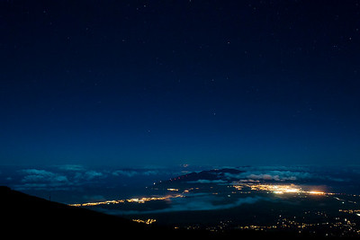 Attempt at star photography. This from the Haleakala summit near midnight. 45 degrees. 10 knot winds. Moon too bright. Well, at least I learned some things.  Bright lights on the right are from Kahalui. On the left from Kehei. On the horizon, from Molokai.