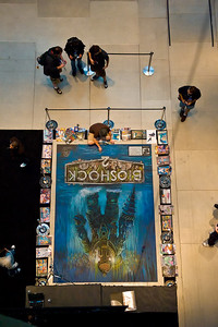Sidewalk artist. He was working on the floor of the trade show lobby doing this photo-realistic rendition of game art.  Here's another view shot from the balcony above.