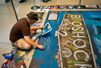 Sidewalk artist. He was working on the floor of the trade show lobby doing this photo-realistic rendition of game art.