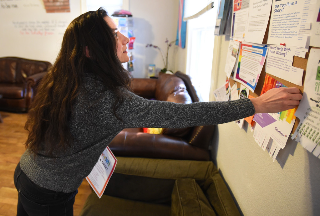 . Michal Duffy, Education and Program Coordinator, puts up a flyer at Out Boulder County in Boulder on Tuesday.  Cliff Grassmick  Photographer January 16, 2018