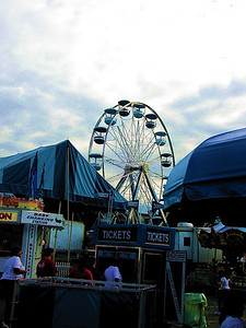 Fair goers are drawn to the Ferris Wheel and the amusement rides like moths to a flame...
