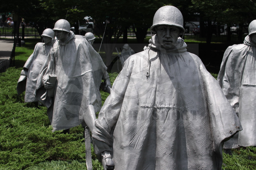 The statues stand in patches of Juniper bushes and are separated by polished granite strips, which give a semblance of order and symbolize the rice paddies of Korea. The troops wear ponchos covering their weapons and equipment. The ponchos seem to blow in the cold winds of Korea.