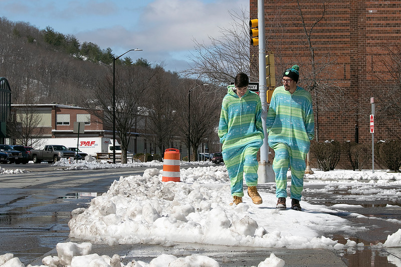 Brennan Teney, 19, and Jimothi Northe, 32 on right, walk down Boulder Drive in Fitchburg in onesies, their coronavirus attire, to get Teney's car that was in the parking garage on Boulder Drive Tuesday, March 24, 2020. SENTINEL & ENTERPRISE/JOHN LOVE