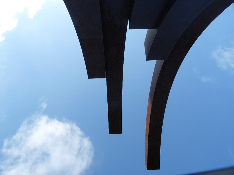 there was one of those wacky curved metal sculptures that look (to me) like upside down spiders at the end of the Marketplace, and I couldn't resist laying on it and taking a shot up at the sky
