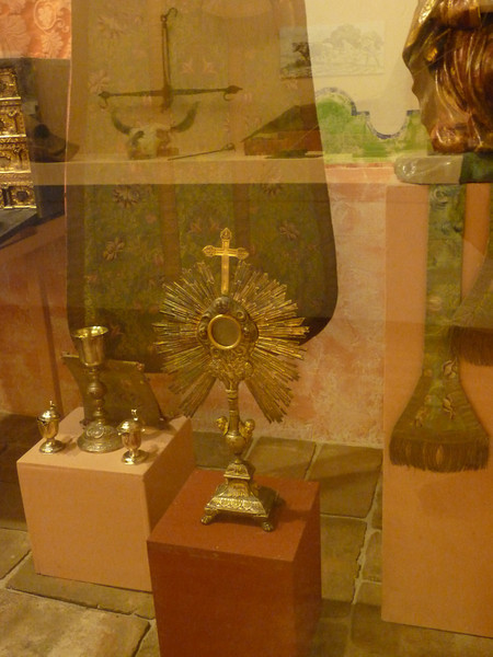 the cow skull is reflected in this shot of some religious artifacts