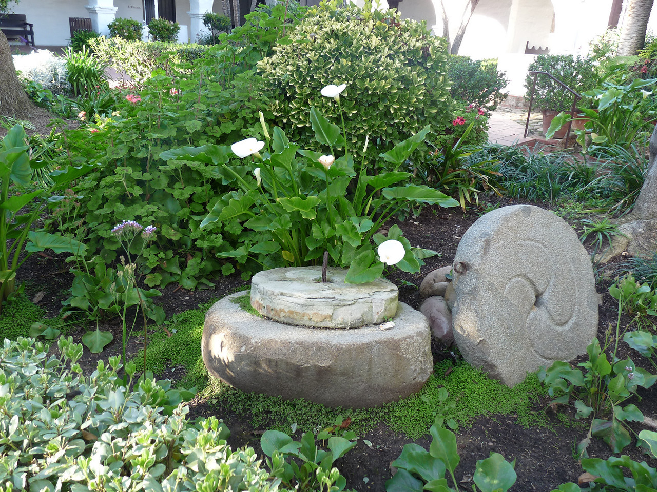 I like this little tableau -- a couple of grindstones in the garden
