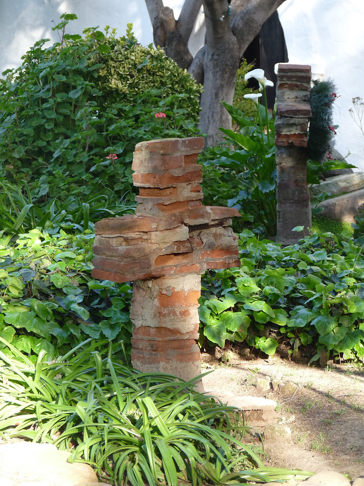 a brick cross in the garden that's really in need of some repair