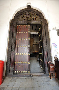 Entrance to the House of Wonders in Stone Town, Zanzibar.  Another example of Arabic Door Architecture with the curved arch surmounting a door with intricate carvings re-inforced with metal projections.