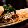 New Summer 2016 Menu Tasting at Pint + Jigger. The Triple B Sandwich. 16-hour braised brisket with Kansas City-style BBQ sauce, P+J slaw and fried kale. © 2016 Sugar + Shake