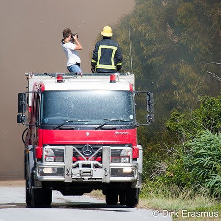 Unknown photographer standing on a fire truck during a bush fire.