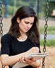 Young Woman sitting on Swing while Sketching on Sketch Pad