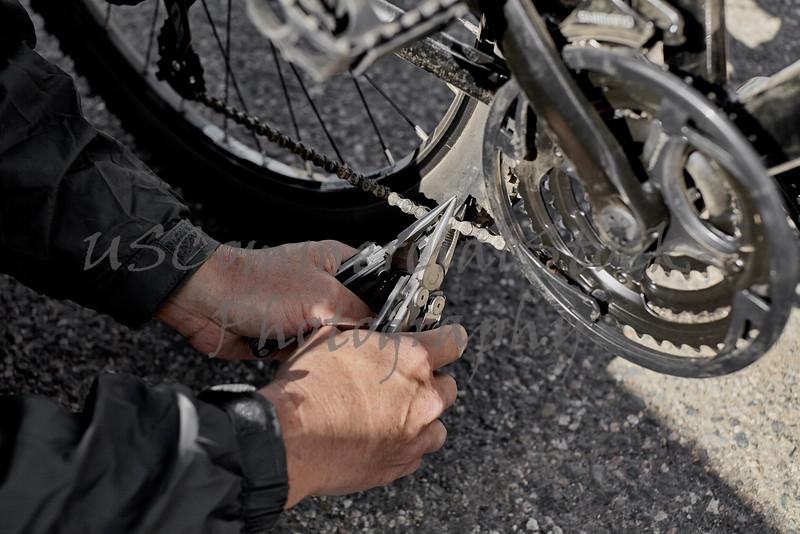 Man's Hand holding Plier on Bike Chain