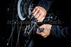 Man adjusting bicycle derailleur gear cable with tools Closeup