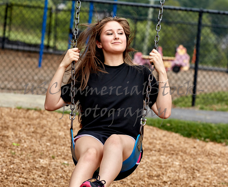 Girl sitting on Swing in Playground