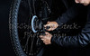 Man adjusting bicycle derailleur gear position with tools Closeup