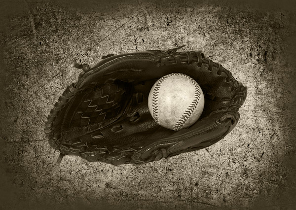 Used Baseball inside a Leather Baseball Glove