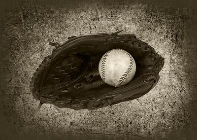 Used Baseball inside a Leather Baseball Glove