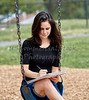 Young Woman sitting on Swing while Sketching on Notebook