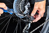 Man adjusting bicycle derailleur gear with tools Closeup