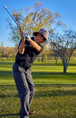 Man golfer fairway iron backswing late afternoon golf round