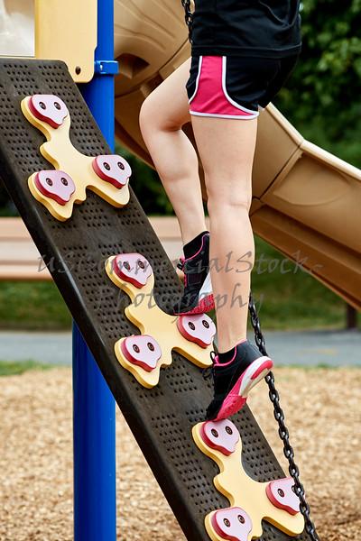 Legs of Girl climbing Playground Equipment