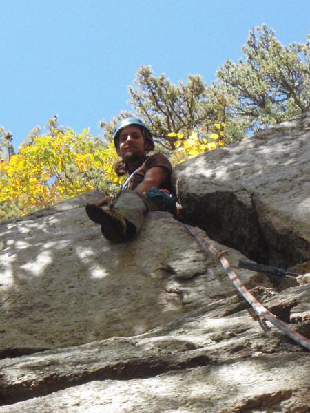 Ben climbing through the crack on Bellyroll (5.4)