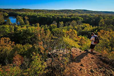 A hiker pauses while gazing out upon the Meramec River from a cliff in Castlewood State Park in Missouri.  Photo by Kyle Spradley | www.kspradleyphoto.com