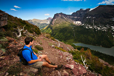 A hiker pauses while along the trail to Triple Divide Pass in Glacier National Park.  Photo by Kyle Spradley | www.kspradleyphoto.com