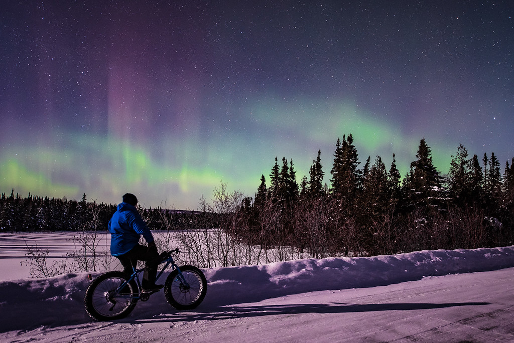 "BIKING 6816<br /> <br /> ""Aurora Borealis Bike Ride""<br /> <br /> What a feeling to be  riding a fat bike on a snowy road illuminated by nothing but moonlight and the glow from the aurora borealis dancing overhead!  This photo was taken at about 1:30 A.M. on February 17, 2016 in the Superior National Forest north of Grand Marais, MN.  What a beautiful night!  I went out in search of the aurora to take pictures of, but I also brought along my bike for a short ride and possible photo op.  I'm glad I brought it because I really like this photo!  I had been riding along one of the gravel forest roads and came upon this clearing with a great view of the sky, so I had to stop for a minute and enjoy the view of the lights."