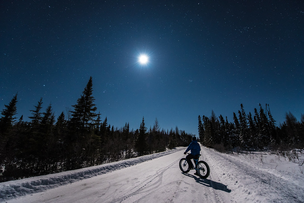 "BIKING 6741<br /> <br /> ""Moonlight Ride in the Superior National Forest""<br /> <br /> February 17, 2016 - Another photo from my moonlight fat bike ride the other night.  This one was taken before the northern lights came out.  I was pedaling down this beautiful forest road bathed in moonlight with a brisk air temp of minus 10 degrees Fahrenheit.  It was a surreal experience!"