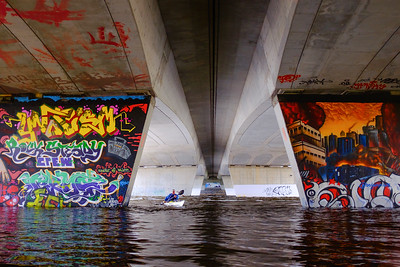 Solo kayaker  entering  the zone of legal graffiti wall art under the Dunbar Bridge in Ottawa, made accessible to paddlers by exceptionally high spring flooding
