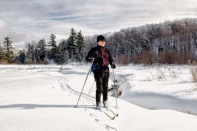 Senior man appreciating the experience while backcountry skiing alongside beautiful creek