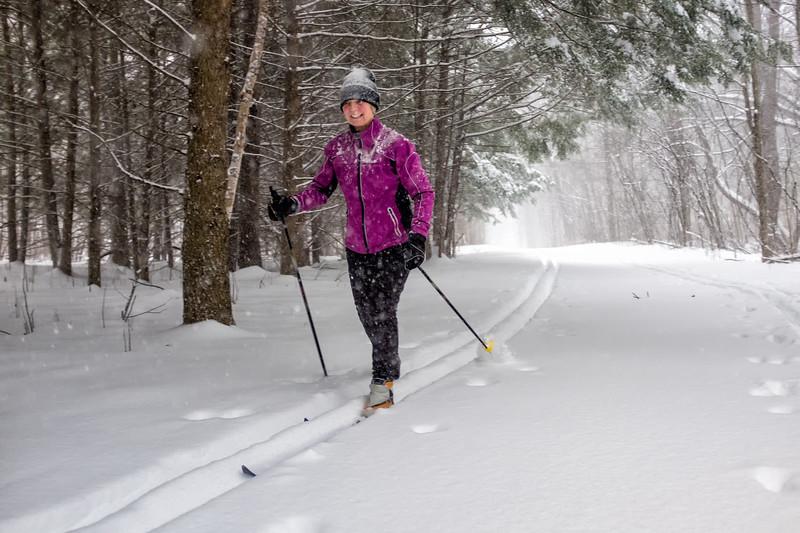 Colorfully sressed senior female enjoying a ski during a snowstorm