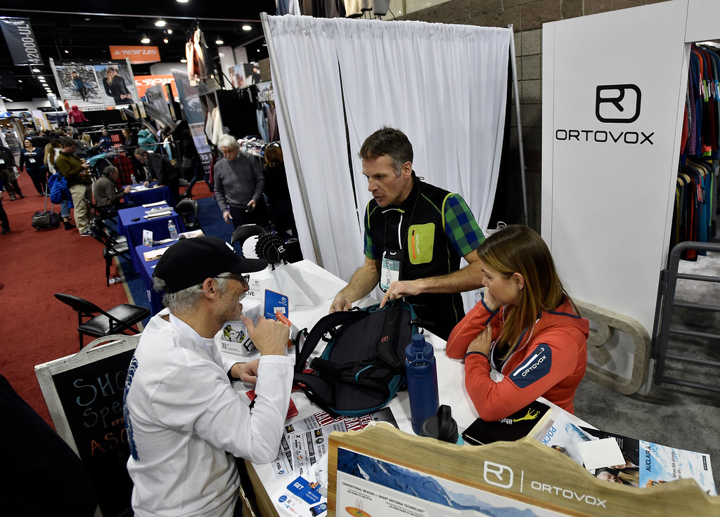 . DENVER, CO - JANUARY 30, 2019: Paul Chessin, with Ikon Pass, left, talks with Ortovox employees Tom Mason and Liz Esche about a backpack during the Outdoor Retailer and Snow Show on Wednesday in Denver. For more photos of Boulder County companies participating in the show go to dailycamera.com (Photo by Jeremy Papasso/Staff Photographer)
