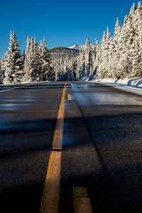 Squaw Pass road extends toward the Mt. Evans massif with long shadows cast by the early morning sun.