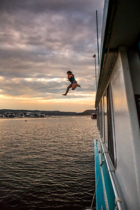A girl jumps from a houseboat at sunset in the marina at Navajo State Park, New Mexico.
