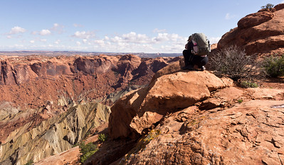 Lynn peering into the abyss. Or at least into a crater at Upheaval Dome.