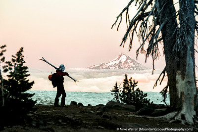 Skier on Mt. Adams, looking at alpenglow on Mt. Hood