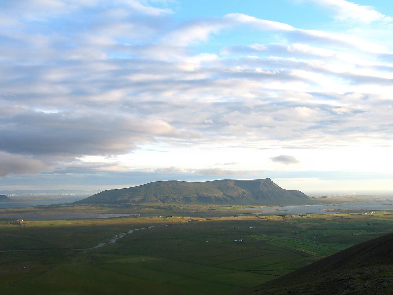 Komin niður úr þokunni, Akrafjall fyrir miðri mynd, vinstra megin við það sér til höfuðborgarinnar.